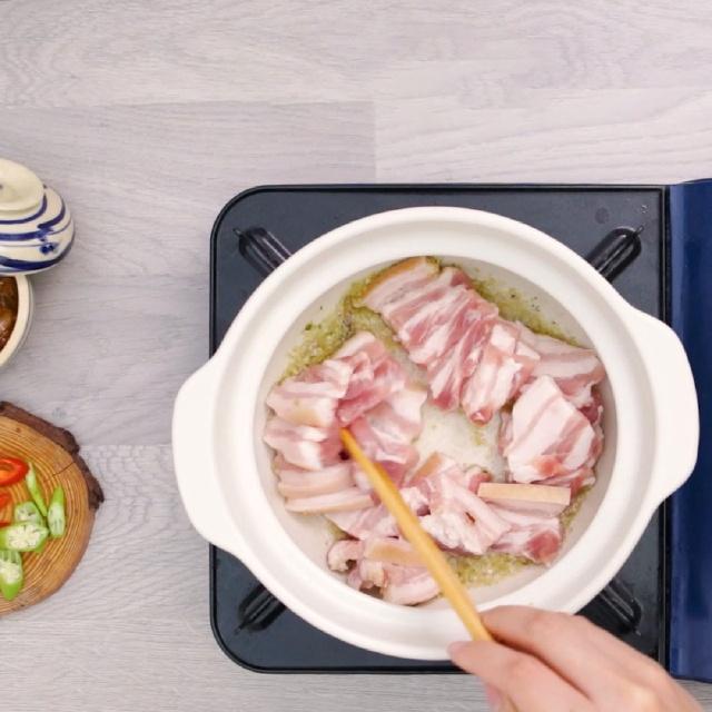 Nấu nước lẩu mắm: Cho 500ml nước lạnh + 500ml nước dừa + 100g mắm cá linh + 100g mắm cá sặc vào nồi rồi bật lên bếp đun sôi ( nếu bạn chỉ mua cá linh không thì vẫn được nhé). Chờ nước sôi cho cá mền khuấy đều cho mắm rã ra, sau đó tắt bếp, dùng vợt để lượt bỏ phần xương cá. Cho phần nước nấu mắm vào nồi nước luộc ở bước trên để tạo thành nước nêm. Bắc chảo lên bếp, cho 3 muỗng canh dầu ăn và phi hỗn hợp tỏi, sả, hành cho thơm vàng. Tiếp theo, ta cho thịt ba chỉ vào xào chung, thêm một muỗng cà phê hạt nêm, đảo đều cho đến khi thịt săn lại là có thể tắt bếp Đổ phần nước nêm vào nồi. Chờ nước sôi thì cho khóm và sả đập dập vào. Nêm 2 muỗng cà phê đường phèn. Chờ khóm mềm thì vớt ra, cho phần cà tím đã xắt sẵn vào nồi, chờ 2 phút thì tắt bếp.